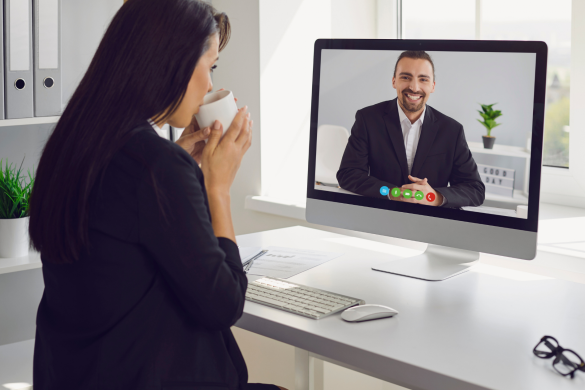 Woman at computer screen being interviewed remotely